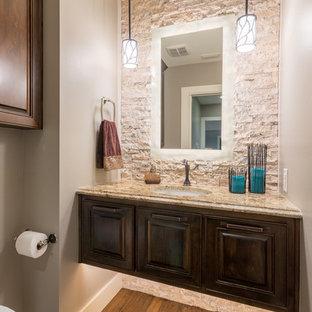 Пример оригинального дизайна: маленький туалет в стиле современная классика с фасадами с выступающей филенкой, темными деревянными фасадами, инсталляцией, бежевой плиткой, каменной плиткой, серыми стенами, паркетным полом среднего тона, врезной раковиной и столешницей из гранита