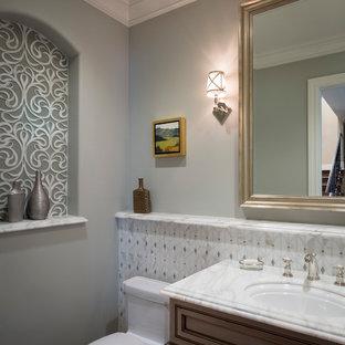 Cette image montre un petit WC et toilettes traditionnel avec un placard à porte affleurante, un WC à poser, un lavabo encastré, un plan de toilette en marbre, des portes de placard en bois sombre, un carrelage blanc, un carrelage de pierre et un mur gris.