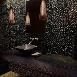 Diseño de aseo rústico con lavabo sobreencimera, encimera de madera, suelo de baldosas tipo guijarro y encimeras marrones