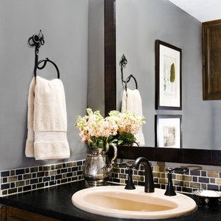 Example of a classic multicolored tile powder room design in Austin with a drop-in sink and black countertops