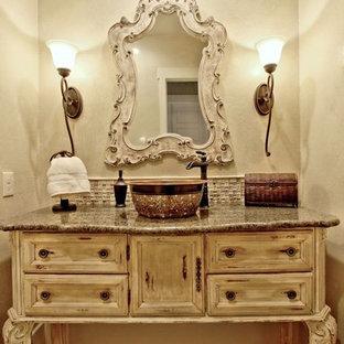 オースティンの中サイズのラスティックスタイルのおしゃれなトイレ・洗面所 (家具調キャビネット、ヴィンテージ仕上げキャビネット、分離型トイレ、ベージュのタイル、ガラスタイル、ベージュの壁、ベッセル式洗面器、御影石の洗面台) の写真