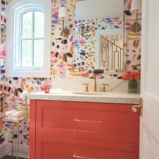 Réalisation d'un petit WC et toilettes bohème avec un placard à porte plane, des portes de placard oranges, un sol en bois brun, un lavabo encastré, un plan de toilette en marbre et un sol marron.