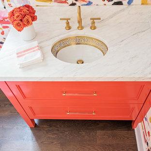 Cette photo montre un petit WC et toilettes éclectique avec un placard à porte plane, des portes de placard oranges, un sol en bois brun, un lavabo encastré, un plan de toilette en marbre et un sol marron.