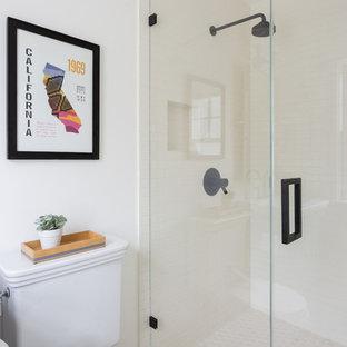 ロサンゼルスの中くらいのコンテンポラリースタイルのおしゃれなトイレ・洗面所 (コンクリートの床、シェーカースタイル扉のキャビネット、グレーのキャビネット、分離型トイレ、白いタイル、サブウェイタイル、白い壁、一体型シンク、マルチカラーの床) の写真