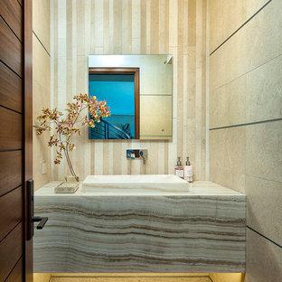 Удачное сочетание для дизайна помещения: туалет в современном стиле с монолитной раковиной, столешницей из оникса, бежевой плиткой, полом из известняка и плиткой из известняка - самое интересное для вас