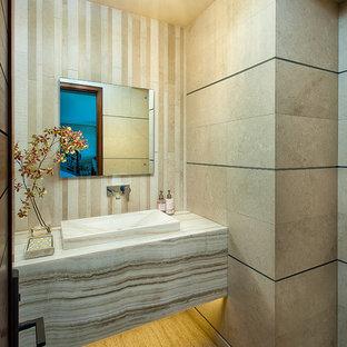 На фото: туалеты среднего размера в современном стиле с монолитной раковиной, столешницей из оникса, бежевой плиткой, бежевыми стенами, полом из известняка и плиткой из известняка