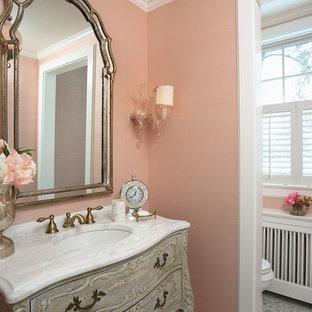 На фото: туалеты среднего размера в викторианском стиле с розовыми стенами, белой плиткой, фасадами островного типа, полом из мозаичной плитки, врезной раковиной и мраморной столешницей