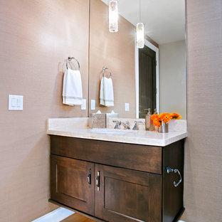 Idée de décoration pour un WC et toilettes tradition de taille moyenne avec un placard avec porte à panneau encastré, des portes de placard en bois sombre, un WC à poser, un mur beige, un sol en travertin, un lavabo encastré, un plan de toilette en travertin et un sol beige.