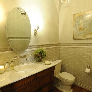 Idées déco pour un WC et toilettes classique de taille moyenne avec un WC séparé, un carrelage beige, un sol en bois brun, un placard à porte shaker, des portes de placard en bois brun, des carreaux de porcelaine, un mur blanc, un lavabo posé et un plan de toilette en marbre.