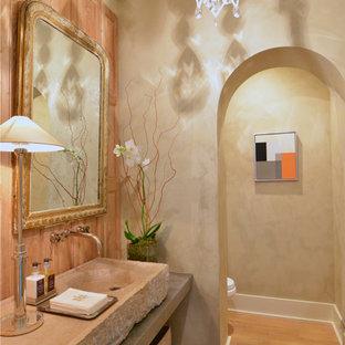 Mittelgroße Gästetoilette mit Wandtoilette mit Spülkasten, beiger Wandfarbe, hellem Holzboden, integriertem Waschbecken, Kalkstein-Waschbecken/Waschtisch und beiger Waschtischplatte in Sonstige