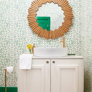 Modelo de aseo clásico renovado con armarios con paneles empotrados, puertas de armario blancas, paredes verdes, suelo de madera en tonos medios, lavabo sobreencimera, suelo marrón y encimeras blancas