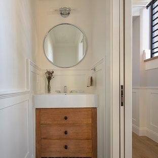 Bild på ett litet lantligt vit vitt toalett, med möbel-liknande, skåp i slitet trä, en toalettstol med separat cisternkåpa, vita väggar, cementgolv, ett avlångt handfat och svart golv