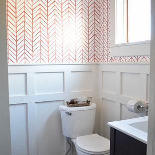 Idee per un piccolo bagno di servizio design con ante lisce, ante in legno bruno, WC monopezzo, piastrelle bianche, pareti arancioni, pavimento con piastrelle in ceramica, lavabo integrato, top in cemento, pavimento grigio e top bianco