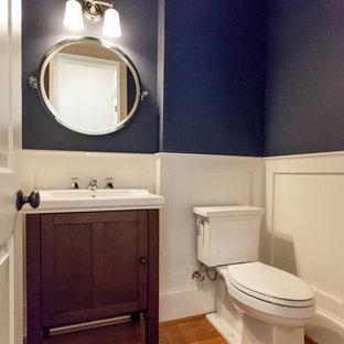 Пример оригинального дизайна: туалет в стиле кантри с фасадами островного типа, темными деревянными фасадами, раздельным унитазом, синими стенами, паркетным полом среднего тона, коричневым полом и белой столешницей