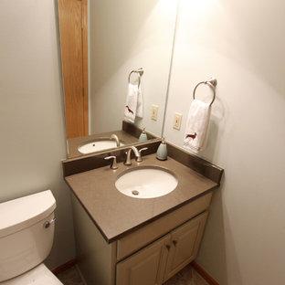 Стильный дизайн: маленький туалет в классическом стиле с фасадами с выступающей филенкой, бежевыми фасадами, раздельным унитазом, зелеными стенами, врезной раковиной, столешницей из искусственного кварца и коричневой столешницей - последний тренд