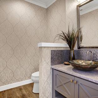 Immagine di un bagno di servizio stile americano con consolle stile comò, ante grigie, WC a due pezzi, piastrelle grigie, piastrelle di vetro, pareti multicolore, pavimento in legno massello medio, lavabo a bacinella e top in marmo