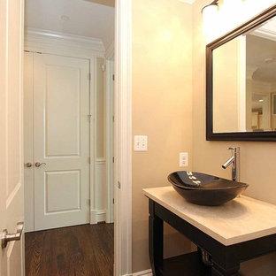 Foto di un bagno di servizio chic di medie dimensioni con nessun'anta, ante in legno bruno, WC monopezzo, pareti beige, pavimento in legno massello medio, lavabo a bacinella e top in travertino