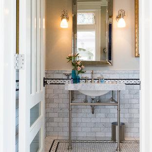 Cette photo montre un grand WC et toilettes bord de mer avec un lavabo de ferme, un carrelage gris, des carreaux de céramique, un mur beige et un sol en carrelage de terre cuite.