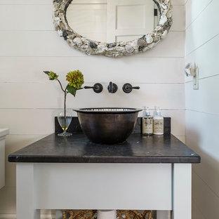 チャールストンの小さいトランジショナルスタイルのおしゃれなトイレ・洗面所 (家具調キャビネット、白いキャビネット、白い壁、ベッセル式洗面器、無垢フローリング、ソープストーンの洗面台、黒い洗面カウンター) の写真
