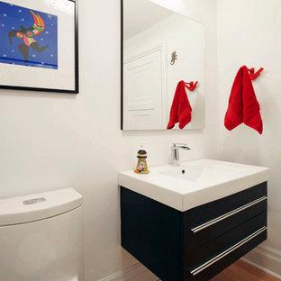 Ispirazione per un piccolo bagno di servizio minimalista con WC monopezzo, pareti bianche, ante lisce, ante nere, pavimento in legno massello medio, lavabo integrato, top in quarzite e pavimento marrone