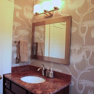 Foto di un piccolo bagno di servizio classico con ante con riquadro incassato, ante in legno bruno, pareti multicolore, lavabo sottopiano, top in granito e top rosso