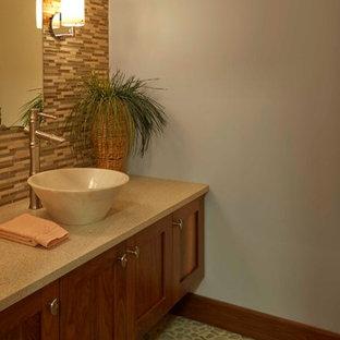 На фото: туалет в современном стиле с фасадами в стиле шейкер, фасадами цвета дерева среднего тона, синей плиткой, бежевой плиткой, полом из галечной плитки, настольной раковиной, столешницей из искусственного кварца и удлиненной плиткой