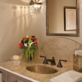 Kleine Urige Gästetoilette mit Unterbauwaschbecken, Schrankfronten mit vertiefter Füllung, hellbraunen Holzschränken, beiger Wandfarbe und beiger Waschtischplatte in Los Angeles