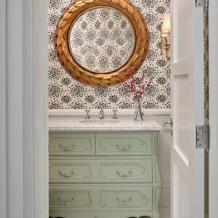 Immagine di un piccolo bagno di servizio chic con consolle stile comò, ante verdi, WC sospeso, pavimento in marmo, lavabo sottopiano, top in marmo e pavimento bianco