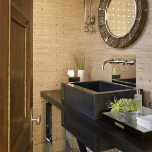 Design ideas for a contemporary cloakroom in New York with freestanding cabinets, beige walls, limestone flooring, a vessel sink and a two-piece toilet.
