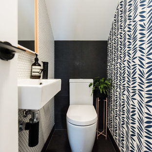 This is an example of a contemporary powder room in Melbourne with a one-piece toilet, mosaic tile, porcelain floors, a wall-mount sink, black floor, white tile and multi-coloured walls.