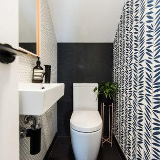 Foto de aseo contemporáneo con sanitario de una pieza, baldosas y/o azulejos en mosaico, suelo de baldosas de porcelana, lavabo suspendido, suelo negro, baldosas y/o azulejos blancos y paredes multicolor