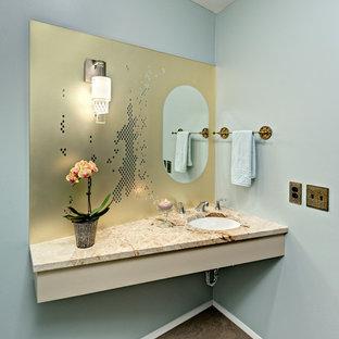 Cette image montre un WC et toilettes design de taille moyenne avec un mur gris, un sol en liège, un lavabo encastré, un plan de toilette en marbre et un sol gris.