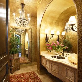 Стильный дизайн: большой туалет в классическом стиле с бежевыми стенами, полом из травертина, врезной раковиной, столешницей из известняка и бежевым полом - последний тренд