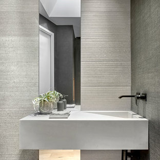 Design ideas for a medium sized modern cloakroom in Chicago with grey tiles, porcelain tiles, grey walls, light hardwood flooring and an integrated sink.