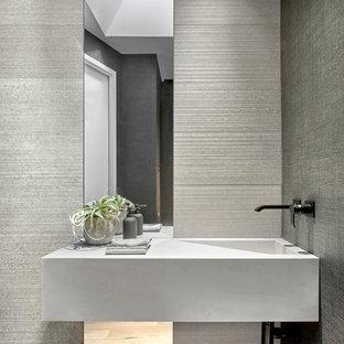 Diseño de aseo moderno, de tamaño medio, con baldosas y/o azulejos grises, baldosas y/o azulejos de porcelana, paredes grises, suelo de madera clara y lavabo integrado
