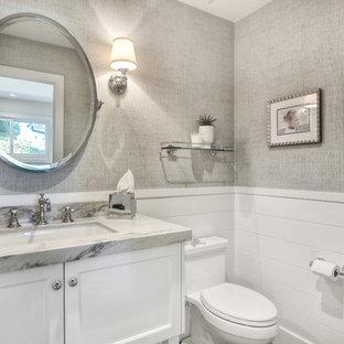 オレンジカウンティの中くらいのトランジショナルスタイルのおしゃれなトイレ・洗面所 (落し込みパネル扉のキャビネット、白いキャビネット、一体型トイレ、グレーの壁、アンダーカウンター洗面器、御影石の洗面台) の写真