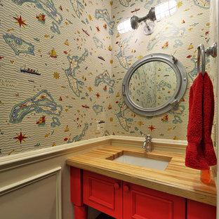 Cette photo montre un WC et toilettes bord de mer avec un plan de toilette en bois, des portes de placard rouges et un plan de toilette marron.