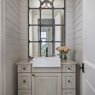 Klassisk inredning av ett litet beige beige toalett, med möbel-liknande, beige skåp, beige väggar, ett fristående handfat och brunt golv