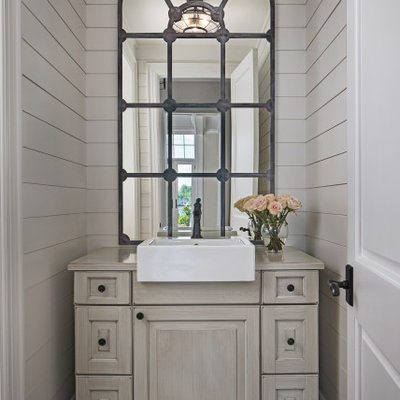 Inspiration for a small transitional brown floor powder room remodel in Detroit with furniture-like cabinets, beige cabinets, beige walls, a vessel sink and beige countertops