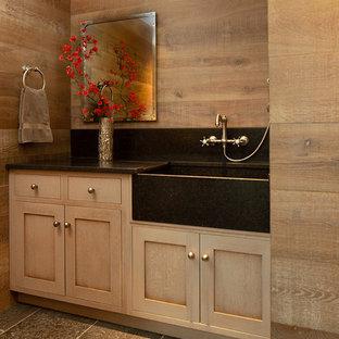 Пример оригинального дизайна: туалет в стиле кантри с фасадами в стиле шейкер, светлыми деревянными фасадами, коричневыми стенами, серым полом и черной столешницей