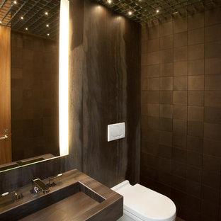 Exemple d'un petit WC et toilettes tendance avec un plan de toilette en marbre, un WC suspendu, un carrelage marron, un mur marron, un sol en calcaire, un lavabo intégré et du carrelage en pierre calcaire.