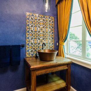 Foto di un bagno di servizio mediterraneo con lavabo a bacinella, nessun'anta, piastrelle multicolore, pareti blu e parquet scuro