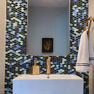 Inspiration för små lantliga toaletter, med en toalettstol med hel cisternkåpa, flerfärgad kakel, glaskakel, blå väggar, mörkt trägolv, ett väggmonterat handfat och brunt golv
