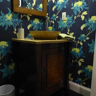 Foto på ett litet funkis toalett, med möbel-liknande, skåp i mellenmörkt trä, en toalettstol med hel cisternkåpa, svart kakel, stenkakel, blå väggar, marmorgolv, bänkskiva i travertin och ett fristående handfat