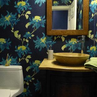 Идея дизайна: маленький туалет в современном стиле с фасадами островного типа, фасадами цвета дерева среднего тона, унитазом-моноблоком, каменной плиткой, синими стенами, мраморным полом, столешницей из травертина и настольной раковиной