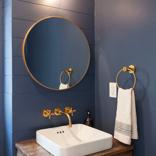 Small country powder room in DC Metro with furniture-like cabinets, medium wood cabinets, blue walls, a pedestal sink, wood benchtops and brown benchtops.