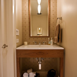 Inspiration for a small contemporary beige tile and porcelain tile porcelain tile and beige floor powder room remodel in San Francisco with an integrated sink, furniture-like cabinets, medium tone wood cabinets, solid surface countertops and brown walls