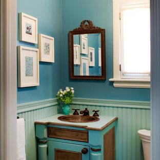 На фото: маленький туалет в классическом стиле с накладной раковиной, фасадами островного типа, бирюзовыми фасадами, столешницей из ламината, синими стенами и паркетным полом среднего тона с