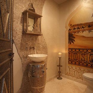 マイアミの中くらいの地中海スタイルのおしゃれなトイレ・洗面所 (ベージュの壁、セラミックタイルの床、ベッセル式洗面器、ベージュのタイル、トラバーチンタイル) の写真