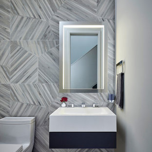 This is an example of a large contemporary cloakroom in Chicago with a one-piece toilet, grey tiles, grey walls and a wall-mounted sink.